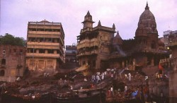 ManikarnikaGhat from the Ganges.  The terraced buildings to the left and center are pilgrim sheds.  The domed temple to the right, now abandoned, was built in the 18th century by Queen Ahalya Bai Holkar of Indore