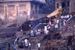 Wood is piled for cremations on the center steps of Manikarnika while families and mourners prepare for the rituals