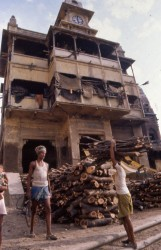 Wood is stacked behind the Birla pilgrim shed by two assistants to the Doms