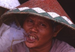 Torajan man smoking clove cigarette in Rontepao